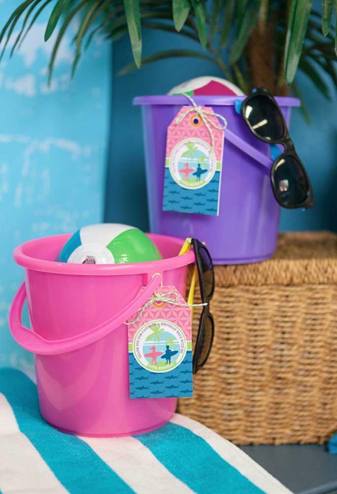 Para a lembrancinha festa na piscina prepare um kit com baldinho de plástico, bola e óculos de sol.