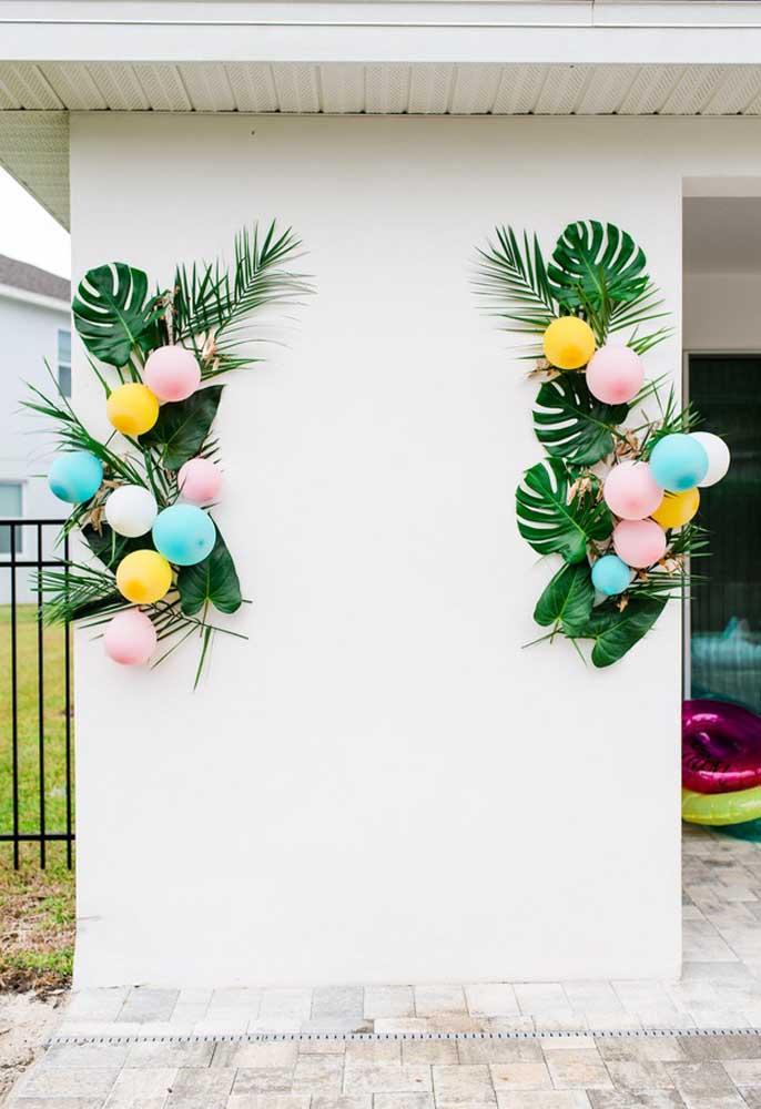 Faça uns arranjos com folhas e balões na entrada da festa na piscina para receber os convidados.