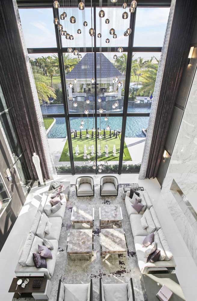 Foto de mansão luxuosa por dentro com vista para a piscina; destaque para o pé direito duplo que realça a grandeza da construção