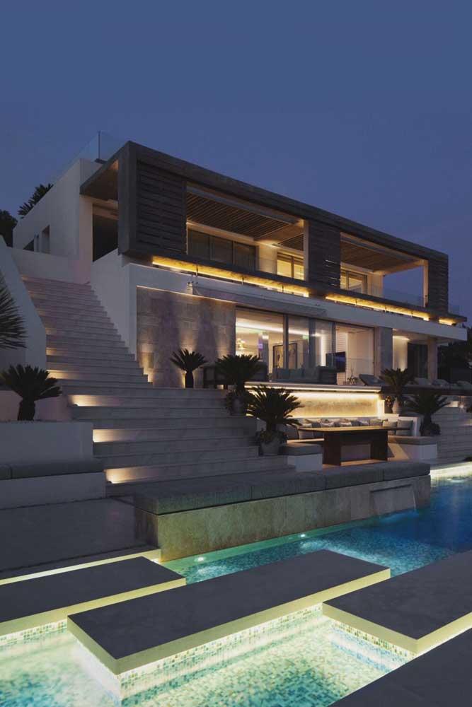 A piscina costuma ser um elemento muito valorizado nas mansões, como essa, que recebeu iluminação especial