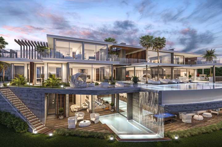 Essa mansão toda feita com paredes de vidro permite visualizar todo seu interior e destacar alguns dos seus cômodos, como a academia privativa com acesso direto à piscina