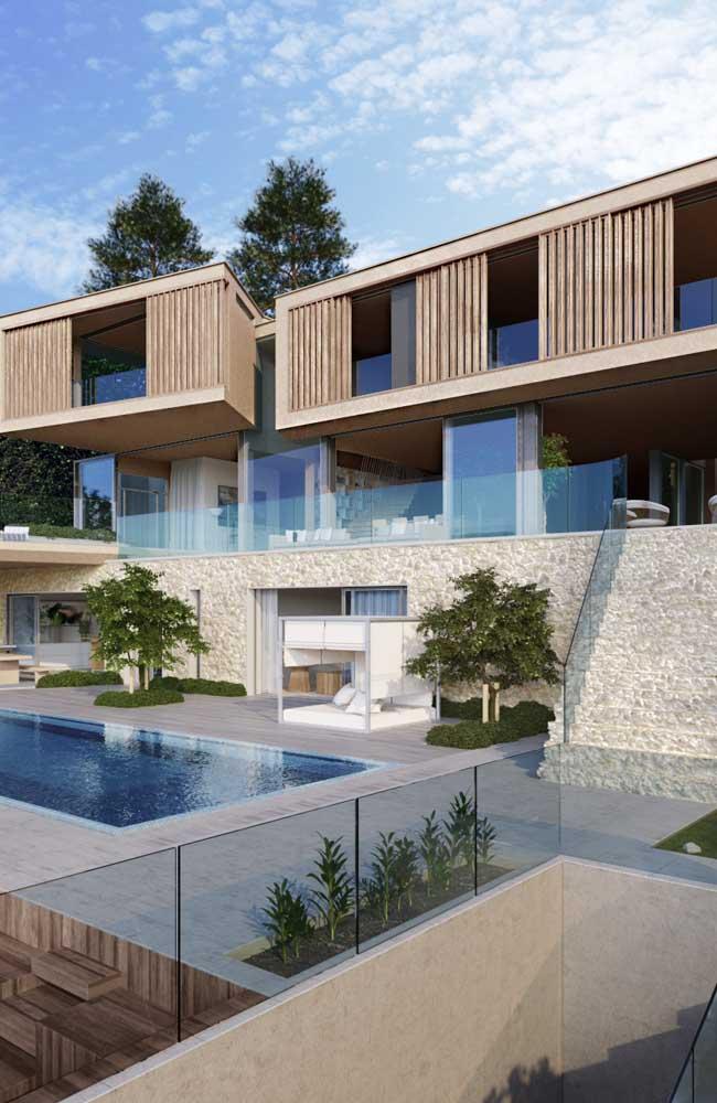 Mansão moderna com mix de materiais na fachada: pedra, vidro e madeira