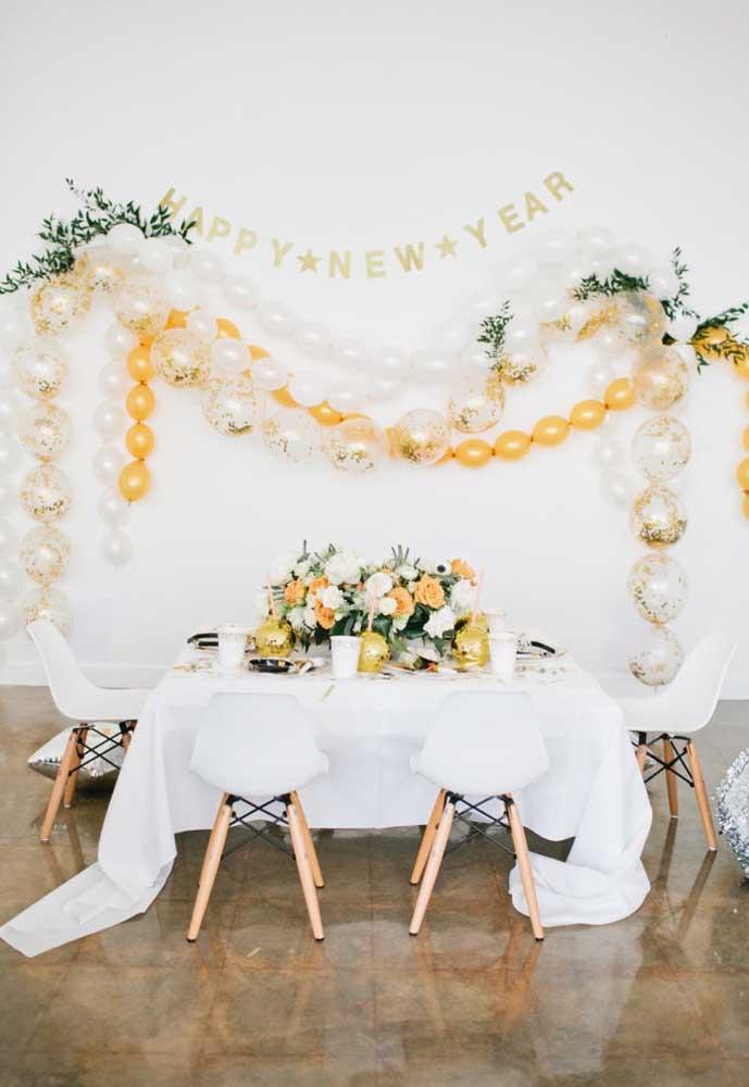 Aposte no arranjo de flores e arcos de balões para fazer a decoração da ceia de ano novo.