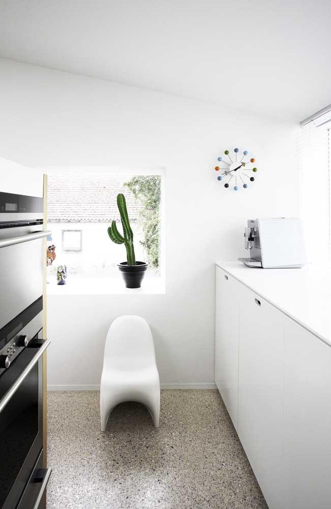 Cozinha clean e moderna decorada com um lindo vaso de cacto; repare que a planta foi colocada no beiral da janela para receber toda a luz necessária para seu desenvolvimento