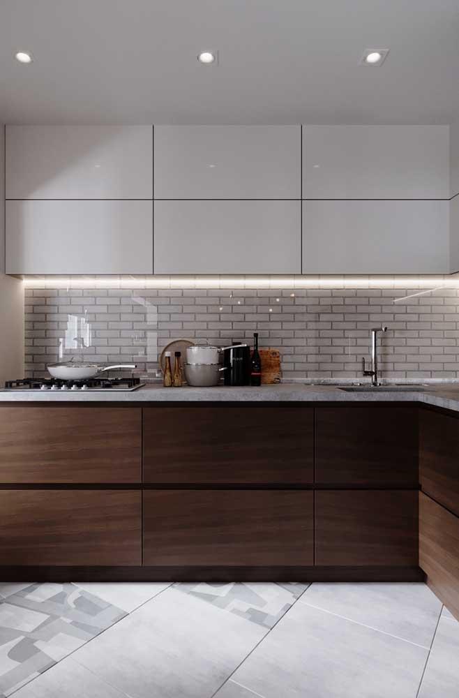 Nessa cozinha, a meia parede em tijolo ecológico ganhou uma proteção em vidro que evita a sujeira e acúmulo de gordura nas peças