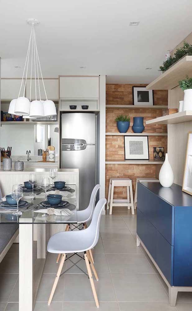 A cozinha integrada ficou muito charmosa com a pequena parede de tijolinhos aparentes