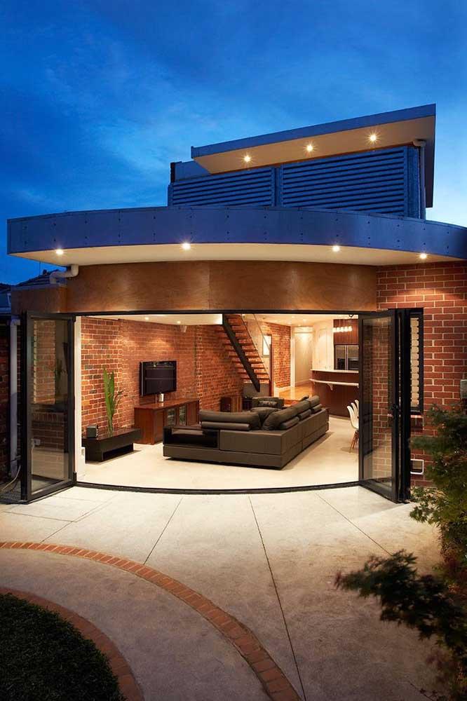 Linda combinação entre o tom natural dos tijolos com o azul royal nos detalhes da casa