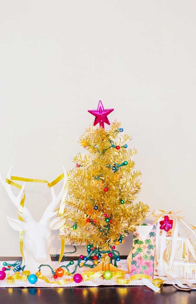 Uma decoração de natal alegre e colorida feita com árvore de natal dourada e bolinhas de várias cores