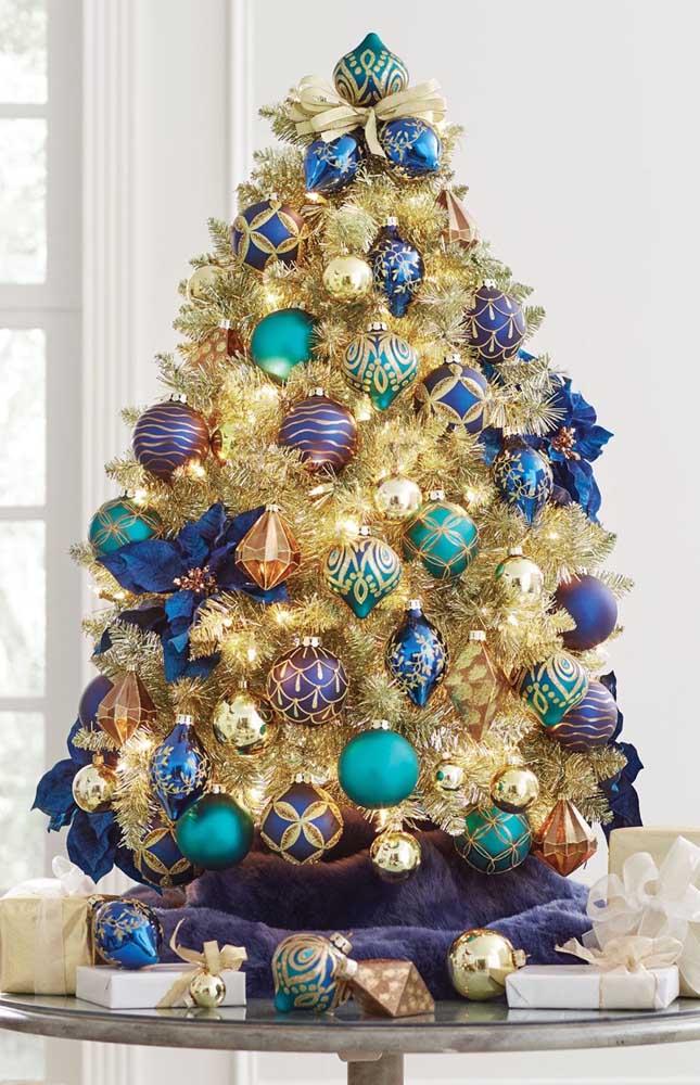 A combinação do dourado com azul na árvore de natal é elegante e luxuosa