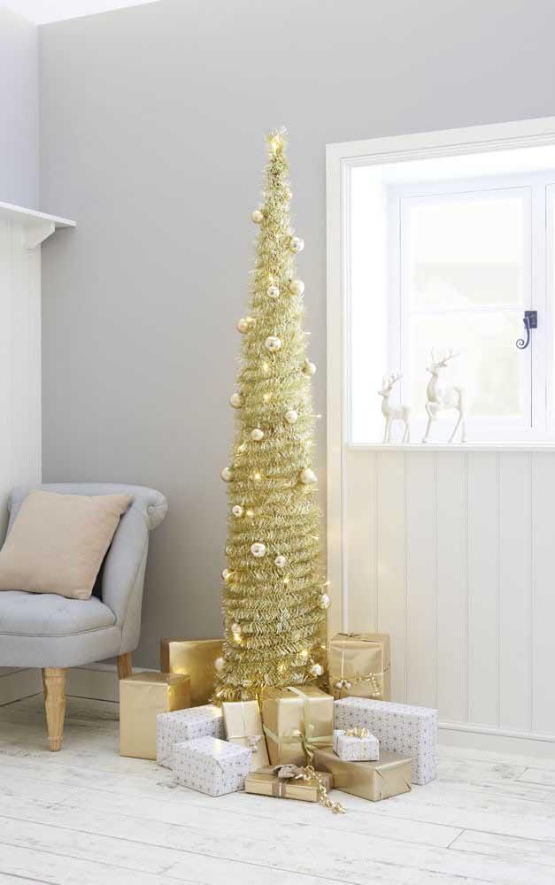Mais esguia, essa árvore de natal dourada acomoda todos os presentes ao seu redor