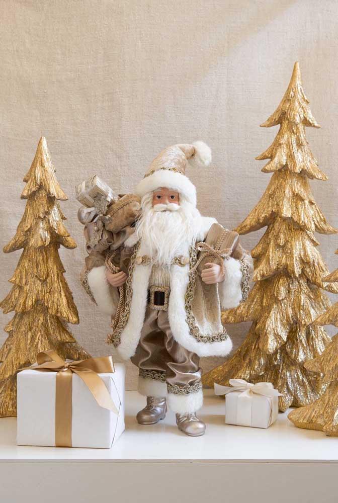 O bom velhinho aparece nessa decoração ao lado das duas árvores de natal dourada