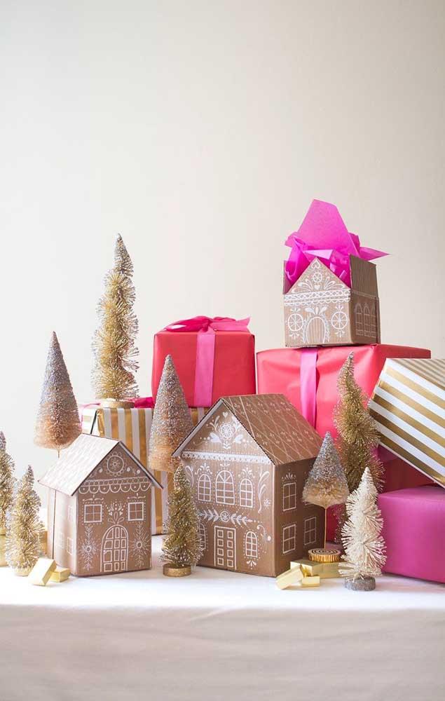 Uma mini cidade feita com as embalagens de presente; para completar, miniaturas de árvore de natal dourada