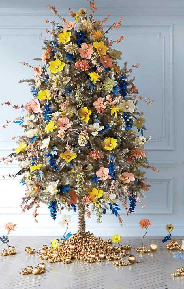 Essa inspiração super diferente de árvore de natal apresenta uma estrutura dourada com enfeites de flores naturais