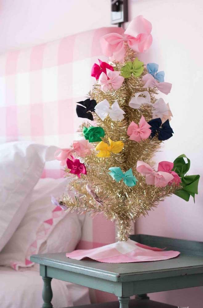 Já essa outra ideia traz uma mini árvore de natal dourada decorada apenas com laços coloridos