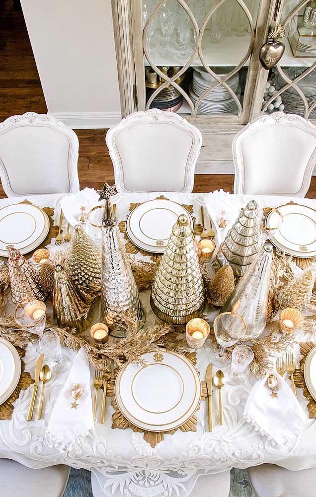 Essa mesa posta para o natal conta com miniaturas de árvore de natal dourada como centro de mesa
