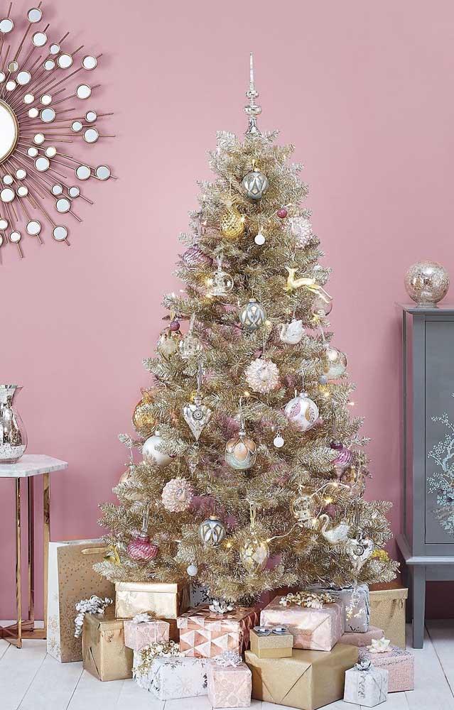 A graça dessa decoração de natal com árvore de natal dourada é a parede rosa aos fundos contrastando com a cor dos enfeites