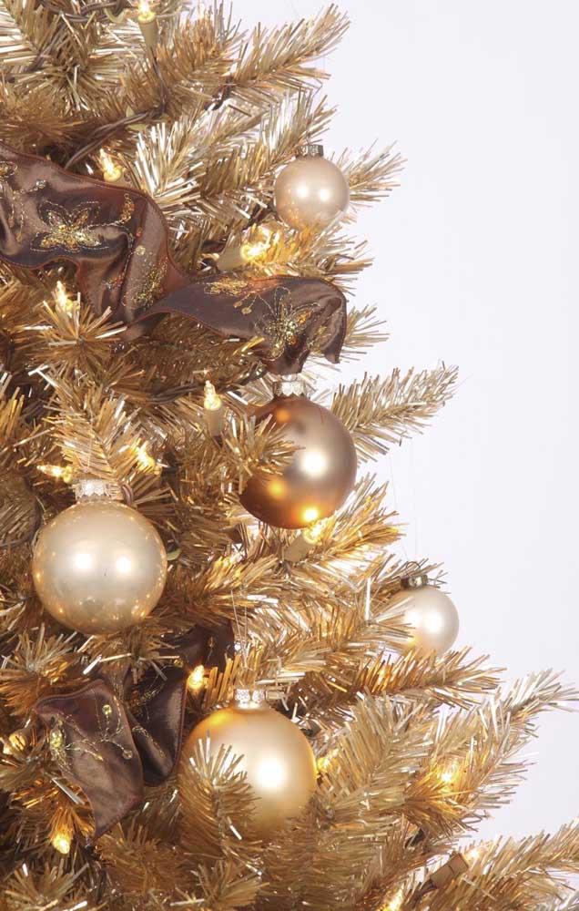Os laços marrons dão um toque a mais de refinamento a árvore de natal dourada