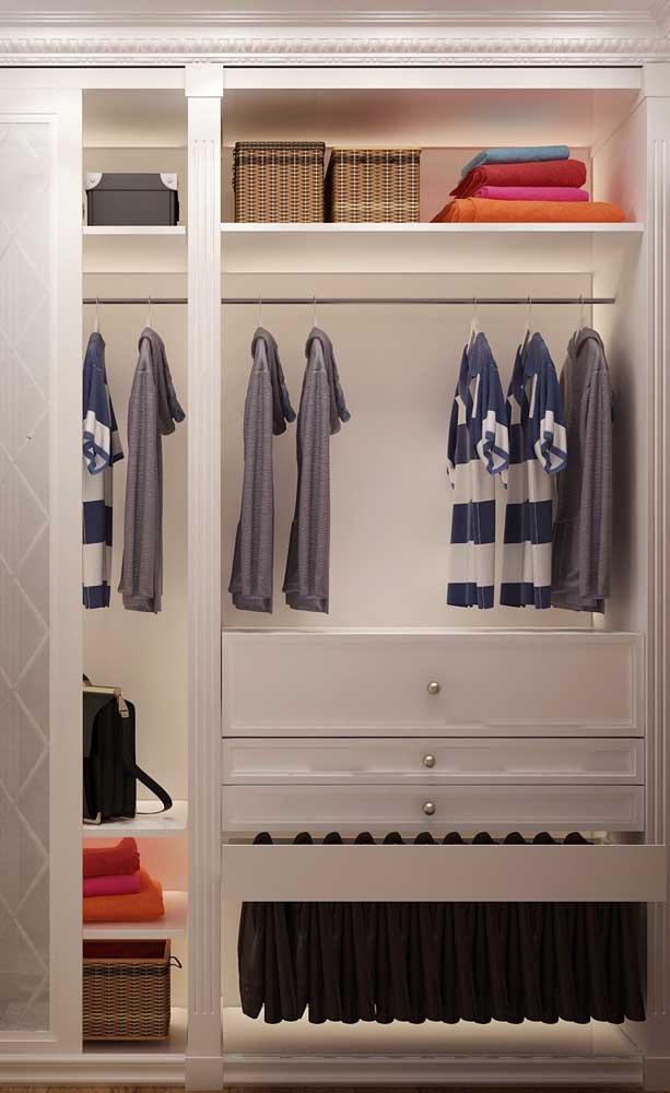 Detalhe de um closet pequeno, com destaque para as gavetas e cabideiros