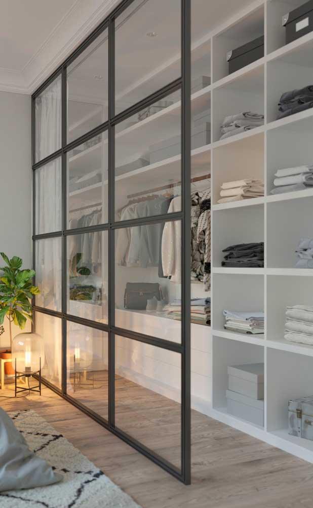 O destaque desse closet vai para a parede de vidro e a cortina que o separa do restante do quarto