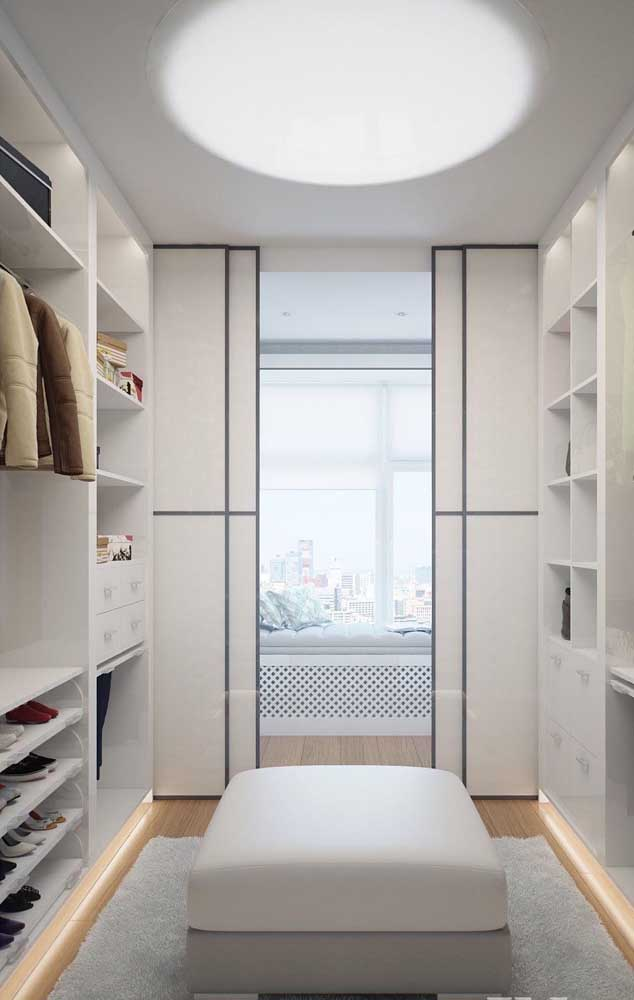 Closet de gesso com portas de correr e um confortável puff no centro