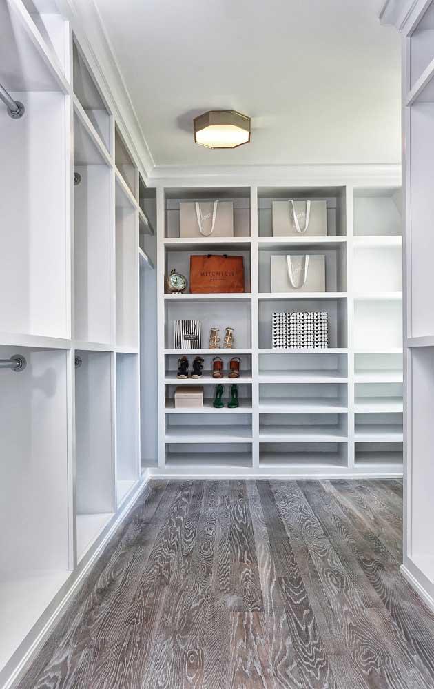 Inspiração de closet de gesso grande com divisórias em diferentes tamanhos; o projeto conta ainda com cabideiros