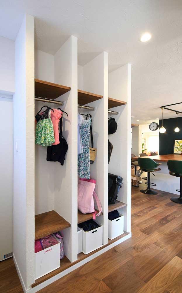 Tipo de closet de gesso aberto para o hall de entrada feito com prateleiras internas de madeira e cabideiros