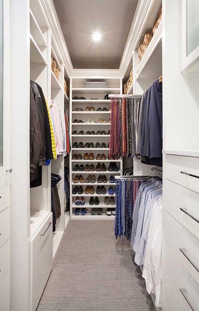 Closet com iluminação em spots e prateleiras específicas para os sapatos, além dos gaveteiros