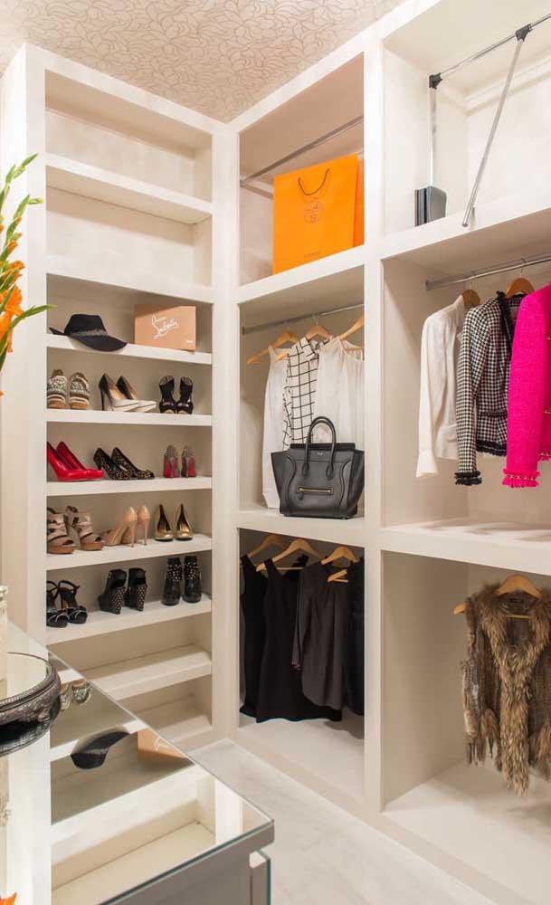 Modelo de closet com penteadeira espelhada e cabideiros diferentes, destaque ainda para as prateleiras que abrigam os sapatos