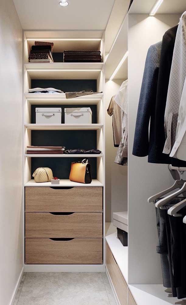 Modelo pequeno de closet com iluminação em fitas de LED para as áreas internas e gaveteiro com portas de madeira