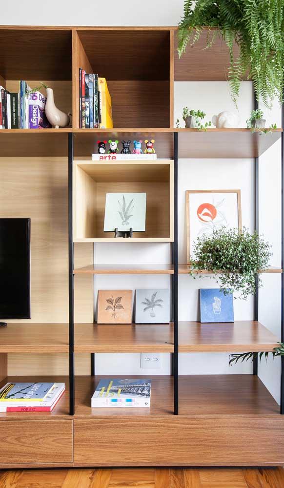 Nichos de madeira embutidos na estante da sala; a união do metal à estrutura garantiu um toque mais moderno ao conjunto