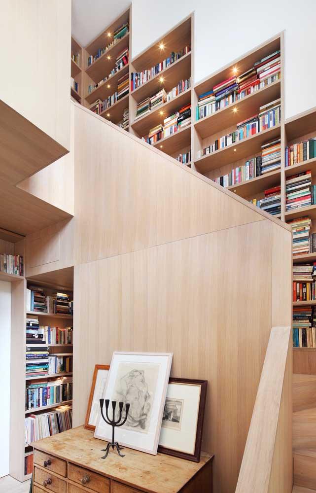 """Nichos de madeira para livros: até aqui nada de novo, o diferencial nesse projeto é que os nichos foram embutidos na parede da escada, ocupando um local geralmente """"morto"""" da casa"""