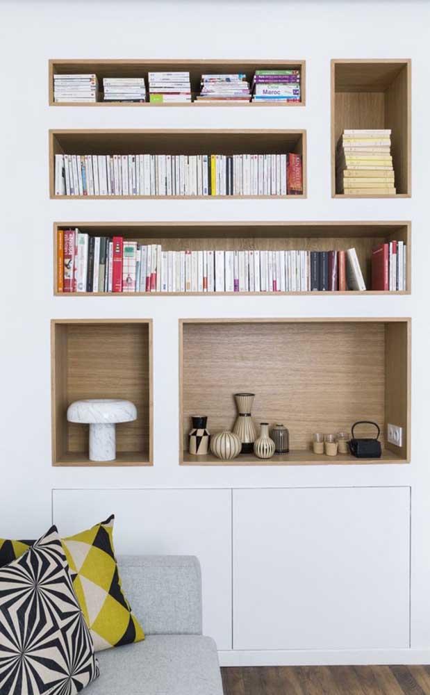 Já nessa sala de estar, os nichos de madeira embutidos foram usados para acomodar os livros