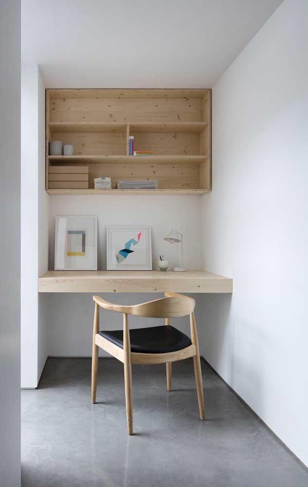 Home office decorado com nichos de madeira em tom cru; o espaço pequeno favorece a utilização das peças