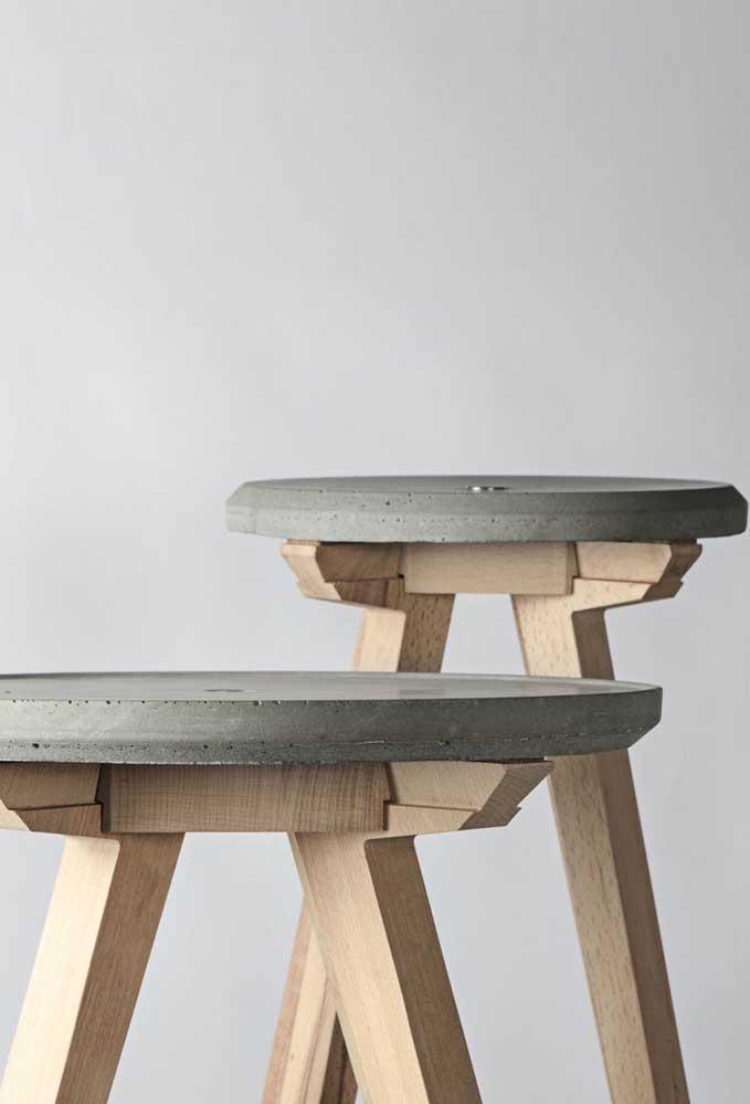 Detalhe de um banco de concreto com pés em madeira; as imperfeições naturais do cimento são parte importante do projeto