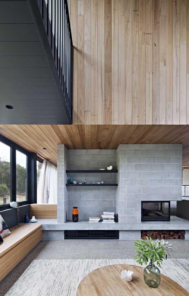 Linda inspiração de sala de estar com parede de tijolos de concreto aparente e banco rústico de cimento queimado; os detalhes em madeira garantem o toque de acolhimento e aconchego ao lugar