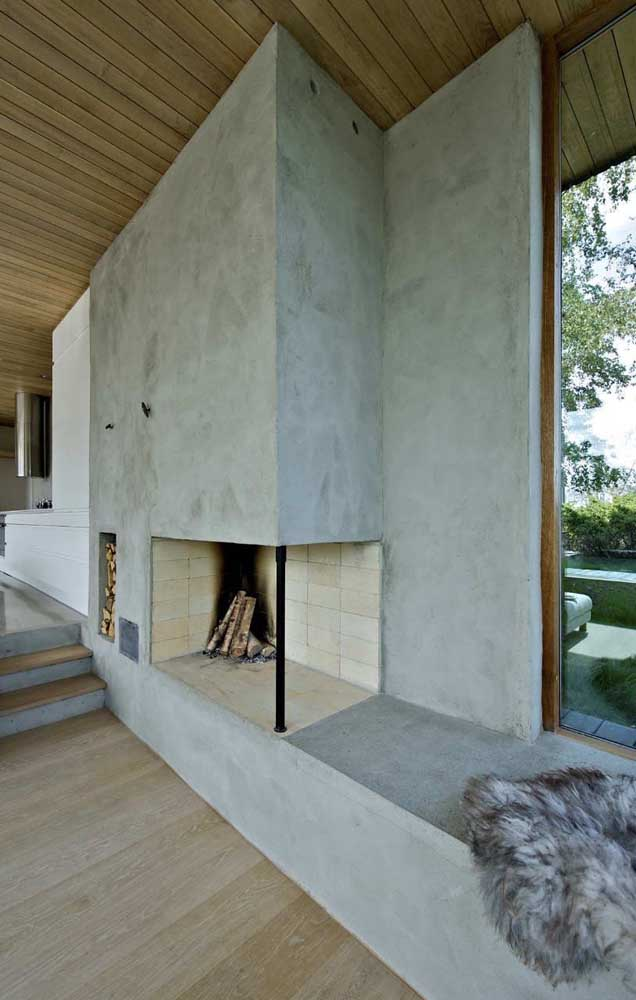 Banco de concreto contornando a área da lareira também feita em concreto e cimento queimado