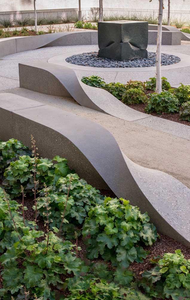 Um banco de concreto super inovador, com formato curvo, orgânico e cheio de movimento