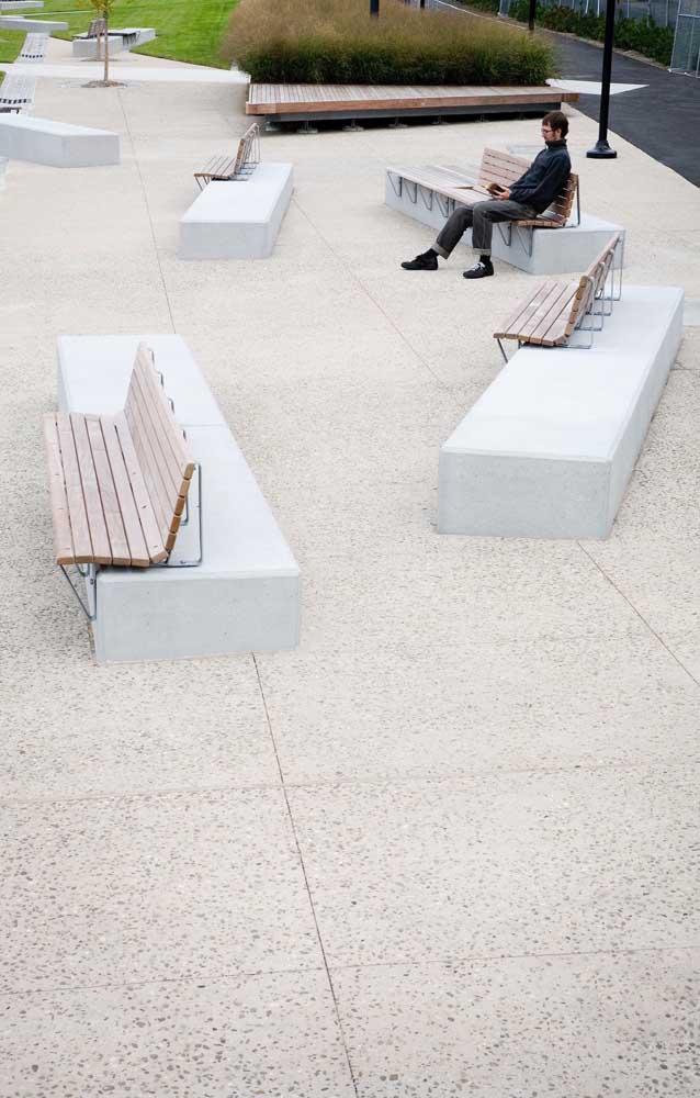 Nessa praça, os tradicionais bancos de madeira ganharam um apoio de concreto garantindo um design super interessante ao espaço