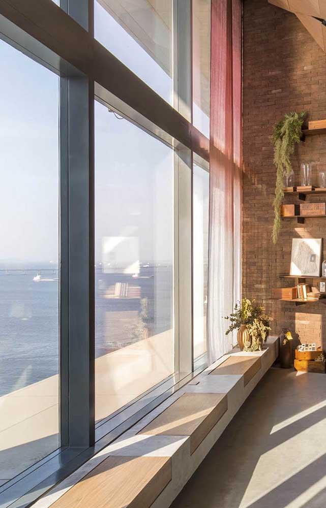 Um banco de concreto colado à janela, pronto para receber os que quiserem passar um tempo apreciando a vista