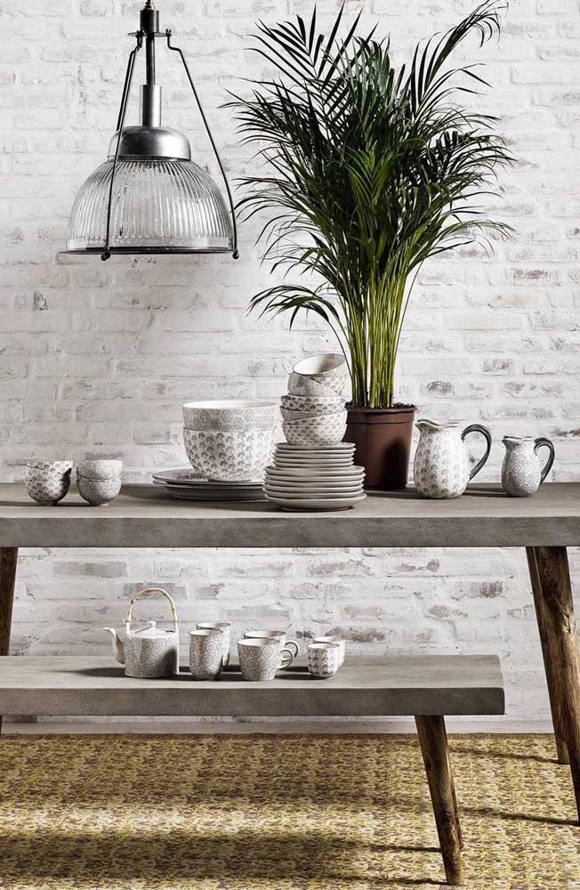 Opção cheia de rusticidade por aqui: conjunto de mesa e banco de concreto com pés de madeira de demolição; a parede de tijolinhos ao fundo completa o cenário