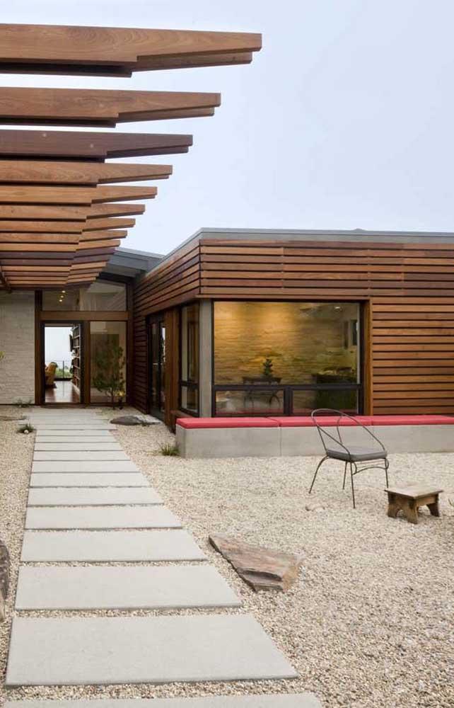 Banco alongado de concreto para a área externa com almofadas vermelhas super contrastantes