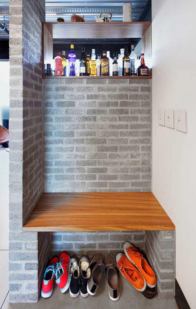 Banco de concreto com assento em madeira no hall de entrada; o vão abaixo do banco ainda funciona como sapateira