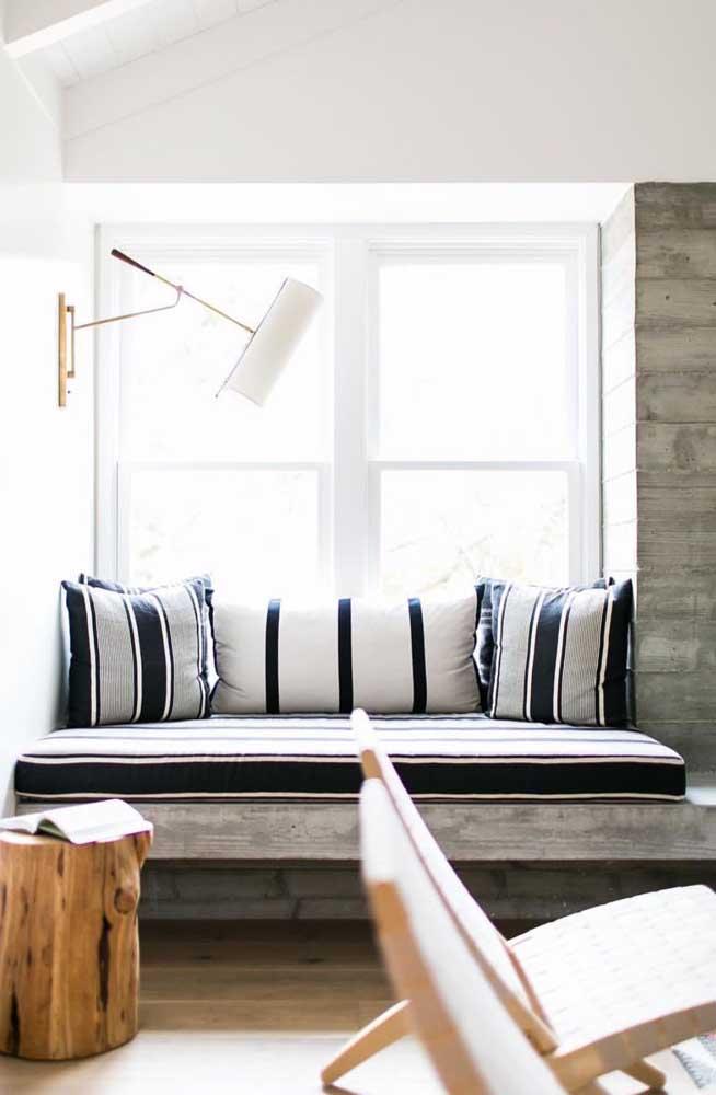 O banco rústico de concreto feito junto à janela foi agraciado com almofadas do tipo futon que garantem mais conforto e beleza à peça