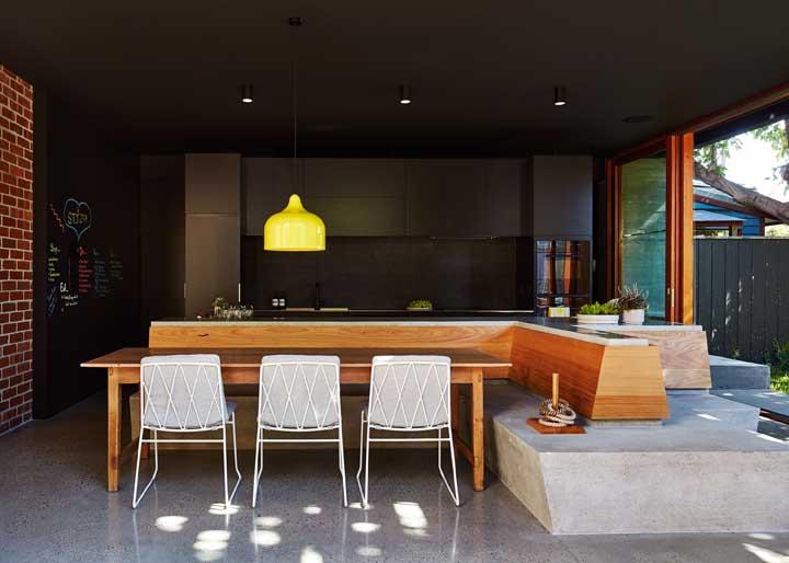 O banco de concreto contorna toda a área desse espaço gourmet externo