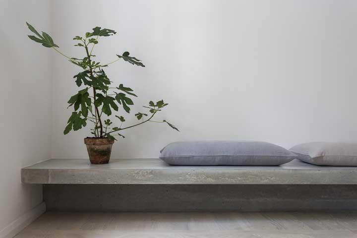 Junto à parede, esse banco de concreto se destaca pela aparência suspensa