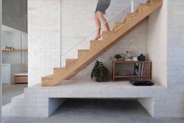 Nessa casa, o espaço embaixo da escada foi aproveitado com um banco de concreto
