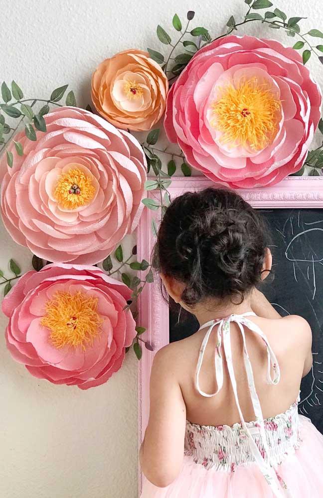 Flores de papel crepom gigantes adornando o quadro lousa infantil