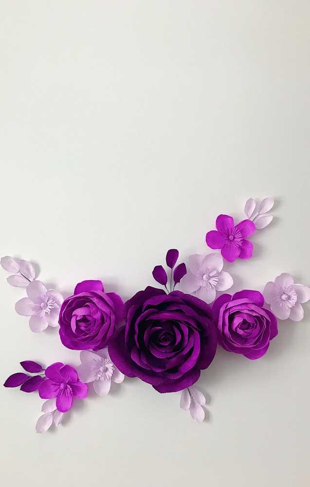 Enfeite de parede feito com flores de papel crepom em tons de roxo e lilás
