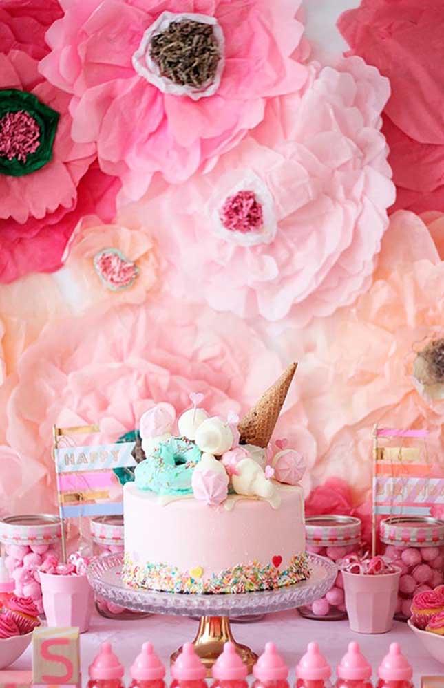 Flores gigantes de papel crepom decoram o painel dessa festa de aniversário com tema de unicórnios