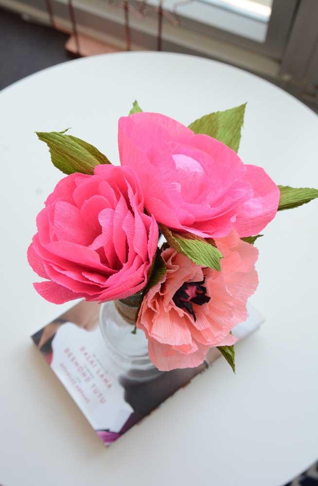 Centro de mesa feito com flores de papel crepom em tons de rosa